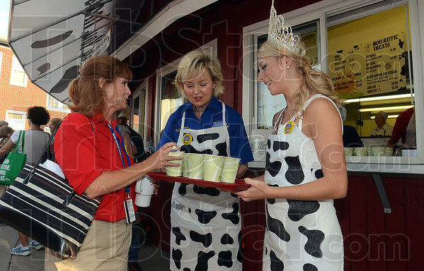 Lt. Governor Becky Skillman, center, and 2012 Indiana State Fair Queen Erika Burghardt of Tippecanoe County offer Anne O'Connor of Indianapolis a free milk shake to celebrate the first day of the state fair Friday in Indianapolis.