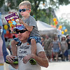 Too much: Five-year-old Hayden James sits on his father's shoulders and reads as they walk along Wabash Avenue Saturday afternoon.