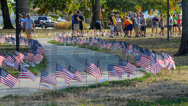 Tribune-Star/Jim Avelis<br /> Good start: Volunteers begin setting flags around the Indiana Mile at Memorial Stadium in Terre Haute Wednesday evening. The Run for the Fallen, commemorating the 6,500 servicemen and women lost so far in Iraq and Afghanistan is this Saturday.