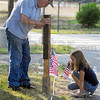 Tribune-Star/Jim Avelis<br /> Teamwork: Jim Fuelle and his granddaughter Julia Goulding work together placing flags at Memorial Stadium in Terre Haute. The hard, dry ground has led several people to come up with new devices to make the pilot holes for the flag sticks. Fuelle is the father of event organizer Olivia Goulding.