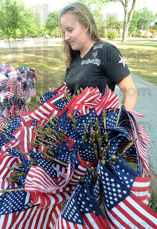 Tribune-Star/Jim Avelis<br /> 6,500: Olivia Goulding carries one of the many bins of flags to its spot around the Indiana Mile at Terre Haute's Memorial Stadium Wednesday evening. The third Run for the Fallen is this Saturday, done in remembrance of those lost in Afghanistan and Iraq. Each of the 6,500 flags bears the name of a fallen service member.
