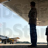 "Tribune-Star/Joseph C. Garza<br /> In the shadow of history: Visitors to the Terre Haute International Airport stand under the right wing of the B-17 Flying Fortress ""Nine O Nine"" as they watch the P-51 Mustang ""Betty Jane"" come to a stop on the tarmac after its arrival Wednesday."