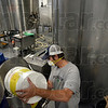 Tribune-Star/Joseph C. Garza<br /> Boiler brewer: Joe Boers, a cellarman at Upland Brewery and a Purdue University graduate , adds more media to a filter Wednesday in Bloomington.
