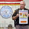 Tribune-Star/Joseph C. Garza<br /> Donation Project: Vermillion County Sheriff Robert J. Spence holds up the poster for the department's AED Donation Project Wednesday during a press conference at the Clinton Municipal Building.