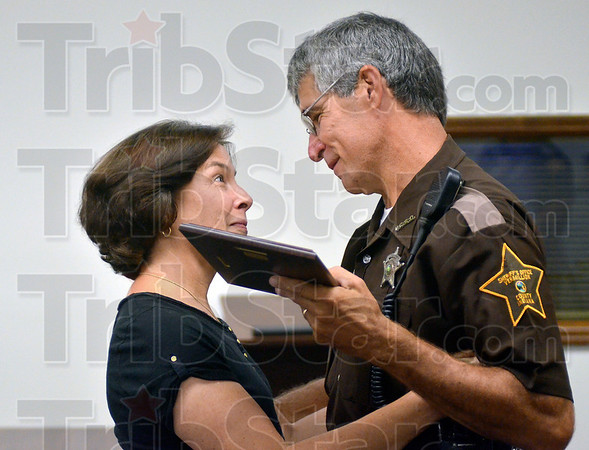 Tribune-Star/Joseph C. Garza<br /> From the bottom of my heart: Vermillion County Sheriff's Deputy Tim DisPennett thanks Rosemary Iacoli as he presents her with a plaque Wednesday at the Clinton Municipal Building. Iacoli revived DisPennett after he collapsed while jogging Aug. 6 in Clinton.