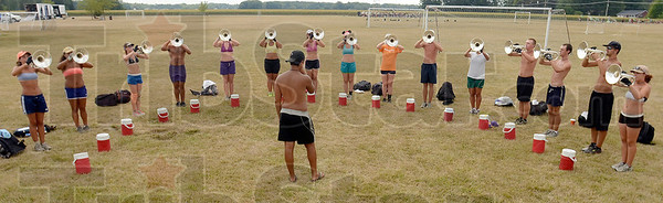 Tribune-Star/Joseph C. Garza<br /> Water cooler array: Members of the Jersey Surf Bugle Corps practice with their water jugs set in front of them Wednesday at North Clay Middle School in Brazil.