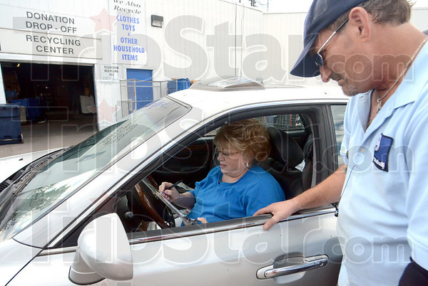 Tribune-Star/Jim Avelis<br /> Making it count: Goodwill donor Maxine Pearman fills out the paperwork needed in order to be able to deduct the fair market value of donated items from her tax return. Goodwill employee Jeffrey Dunning is on the right.
