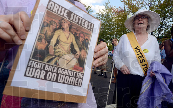 Tribune-Star/Joseph C. Garza<br /> Celebrating the right to vote: Zann Carter holds a poster that calls for action as Cathy McGuire wears suffragette period dress before the start of the Women's Equality March Monday on the Indiana State University campus.