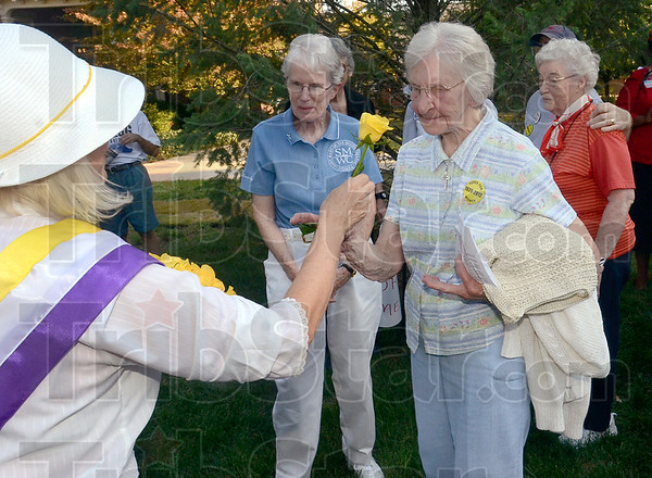 Tribune-Star/Joseph C. Garza<br /> For our long time voters: Carolyn Callecod, president of the League of Women Voters of the Wabash Valley, hands a flower to Sister Mary Ann Lechner, S.P. to honor her for the decades that she has been a registered voter after the Women's Equality March Monday on the Indiana State University campus.