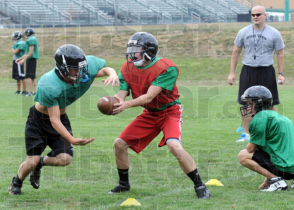 Hand-off: West Vigo assistant coach Troy Isles (R) watches as quarterback Hunter Voils hands the ball off during Monday's first practice of the season.