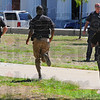 Tribune-Star/Jim Avelis<br /> On the way: Law enforcement officers run to the south side of the Vigo County courthouse where family members of shooting victim Dustin Kelly were being escorted away from the area.