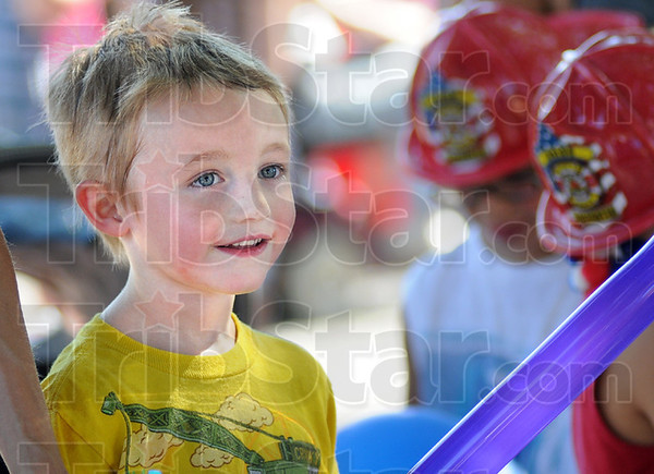 Smile: Five-year-old C. J. Mount is smiles as he watches a clown make him a balloon sword during Tuesday's National Night Out event at Fairbanks Park.