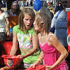 Water world: Hannah and Courtney Stewart pour water over their heads to cool down during Tuesday's National Night Out event at Fairbanks Park.
