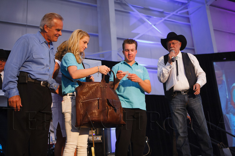 "Jim and Emma Galbreath have Tanner Seebaum draw the winning ticket for the flight to Napa, California, with the winner to be announced by Gary Corbett.  ""SaddleUp! and Pack Your Bags"" event, benefiting the SaddleUp! Foundation at the Mayo Aviation Hangar, Centennial Airport, in Centennial, Colorado, on Friday, Aug. 17, 2012.<br /> Photo Steve Peterson"