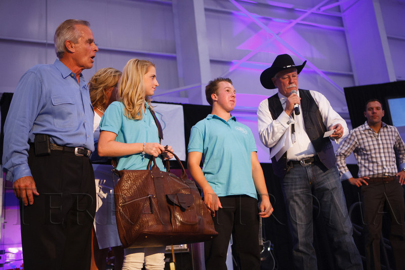 "Jim and Emma Galbreath have Tanner Seebaum draw the winning ticket for the flight to Napa, California, with the winner being announced by Gary Corbett.  ""SaddleUp! and Pack Your Bags"" event, benefiting the SaddleUp! Foundation at the Mayo Aviation Hangar, Centennial Airport, in Centennial, Colorado, on Friday, Aug. 17, 2012.<br /> Photo Steve Peterson"