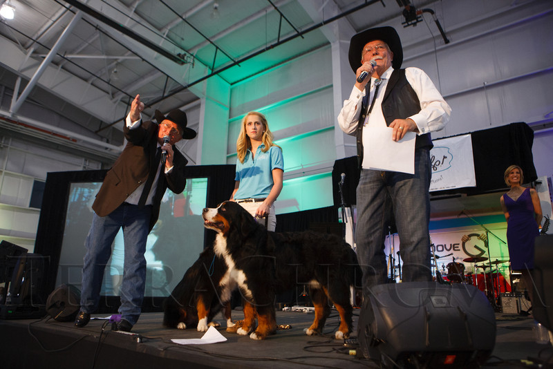"""Adam Kevil and Gary Corbett (right) call the live auction, with Emma Galbreath and Bernese mountain dogs to encourage the bidders.  """"SaddleUp! and Pack Your Bags"""" event, benefiting the SaddleUp! Foundation at the Mayo Aviation Hangar, Centennial Airport, in Centennial, Colorado, on Friday, Aug. 17, 2012.<br /> Photo Steve Peterson"""