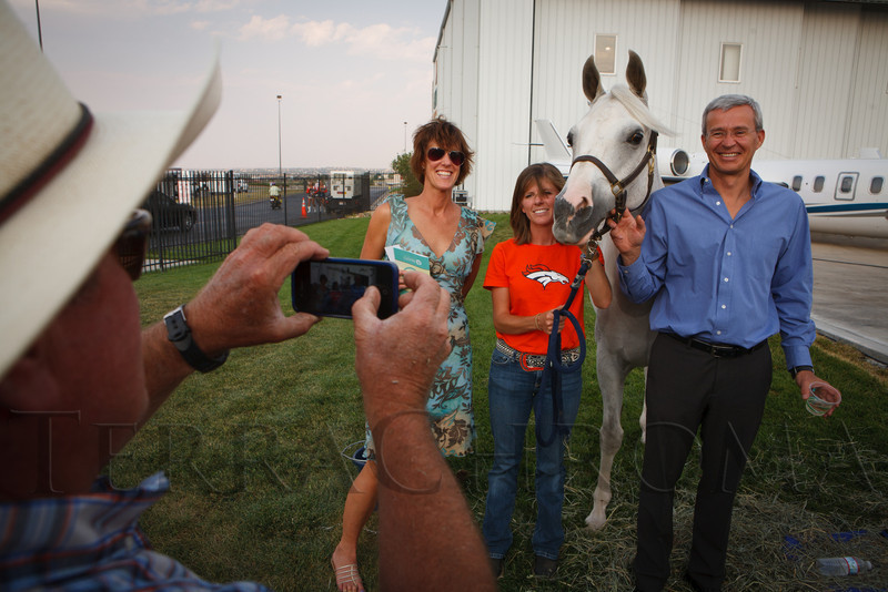 "Paula and Igor Serbinin pose with Thunder. Taking the picture is Terry Wegener and handling Thunder is Mandy Griffey.  ""SaddleUp! and Pack Your Bags"" event, benefiting the SaddleUp! Foundation at the Mayo Aviation Hangar, Centennial Airport, in Centennial, Colorado, on Friday, Aug. 17, 2012.<br /> Photo Steve Peterson"