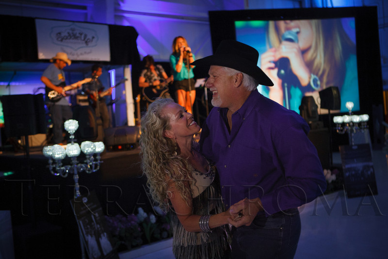 "Elizabeth Owens and fiance Jace Glick dance to Jessie James.  ""SaddleUp! and Pack Your Bags"" event, benefiting the SaddleUp! Foundation at the Mayo Aviation Hangar, Centennial Airport, in Centennial, Colorado, on Friday, Aug. 17, 2012.<br /> Photo Steve Peterson"