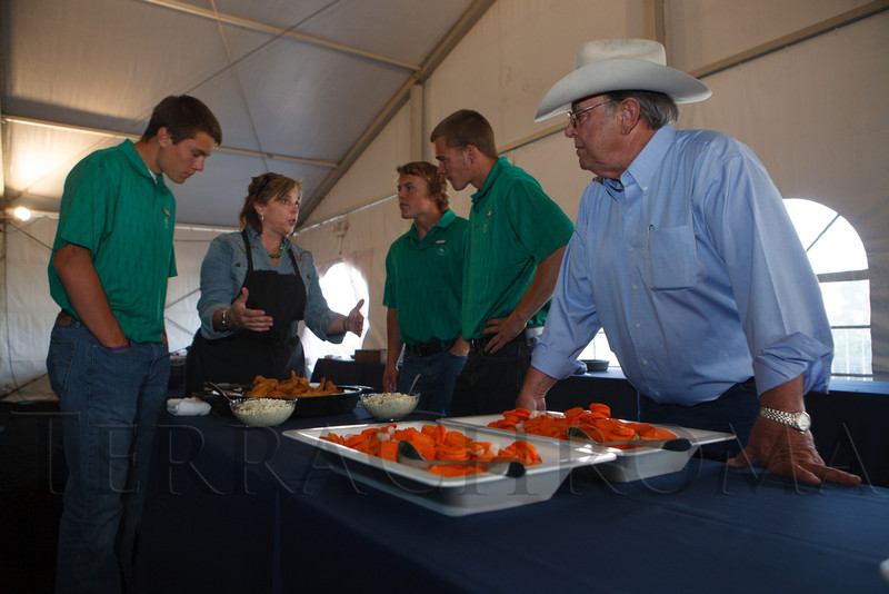 Volunteers Brandon Belk, Brandon Coffelt, and Zach Taylor, get some foodservice instructions from event caterers Lisa and Tom Perini (right), founders of the Perini Ranch Steakhouse in Buffalo Gap, Texas.  Lulu's Barkin' BBQ, benefiting the Dumb Friends League Buddy Center in Castle Rock, Colorado, held at the home of Fred and Jana Bartlit in Castle Pines, Colorado, on Saturday, Aug. 18, 2012.<br /> Photo Steve Peterson