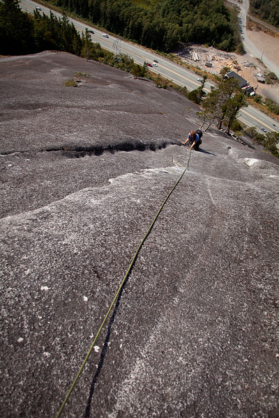 The giant slab of The Apron falls away below Tracy as she nears the final pitch of <i>Banana Peel 5.8</i> on the Stawamus Chief.