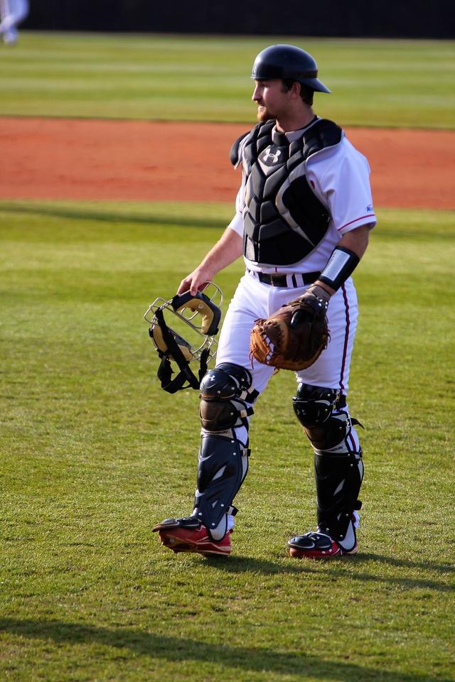Catcher, John Harris, walks back to home plate