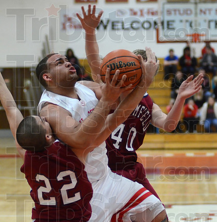 Tribune-Star/Jim Avelis<br /> Unstoppable force: Jeffrey Turner draws a foul from Bloomfield's Ben Hays as fellow Cardinal Kyle Robinson(40) tries to slow him down from behind. Turner made the shot and a free throw.