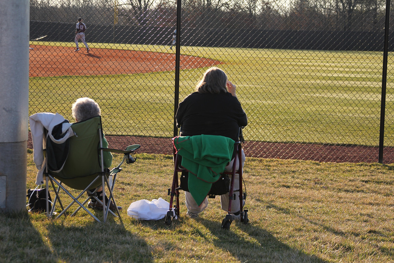 Two elderly women watch the game away from the loud crowds at the bleachers.