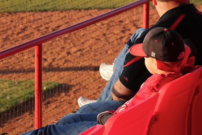 Little boy watches the gwu baseball team with family member.
