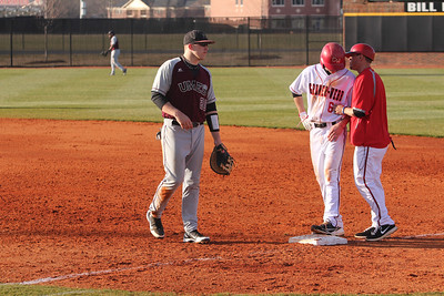 Player 6, Ryan Hodge, listens to advice while on first base.