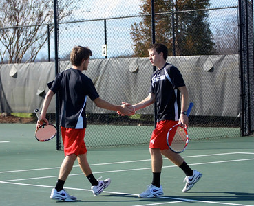 GW Tennis teamates high five each other after a good play