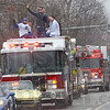 Super hero: Steve Weatherford (black jacket)  waves to fans as he rides a fire engine along Wabash Avenue Friday afternoon.