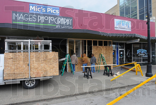 Tribune-Star/Jim Avelis<br /> Still open: A construction crew builds a temporary wall across the fronts of Mics Pics/Images Photography and the Blu Katt Lounge on Wabash Avenue in downtown Terre Haute. An early Friday morning accident damaged both businesses that remain open for business.