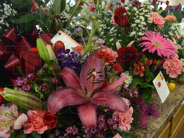 Tribune-Star/Jim Avelis<br /> Ready to go: Dozens of vases of flowers wait for Cowan & Cook Florists delivery van driver Debbie Cagle to take them around the city.