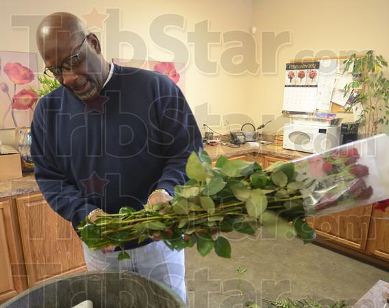 Tribune-Star/Jim Avelis<br /> Snip: Curtis Lyle prepares roses for his designers to arrange into bouquets at Cowan & Cook Florist.