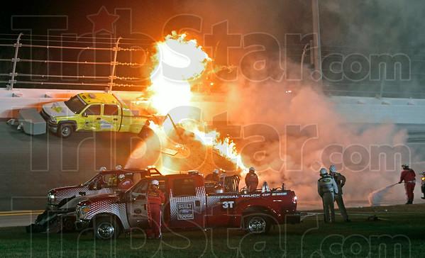 Emergency workers try to put out a fire after Juan Pablo Montoya's car struck the truck during the NASCAR Daytona 500 auto race at Daytona International Speedway in Daytona Beach, Fla., Monday, Feb. 27, 2012. (AP Photo/Bill Friel)