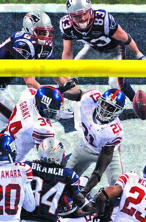 New York Giants safety Kenny Phillips (21) watches as a pass from New England's Tom Brady floats through the air during the final play of Super Bowl XLVI Sunday in Indianapolis. None of the Patriot receivers caught the ball and the game ended with the Giants as the victors.