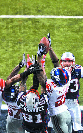New York Giants safety Kenny Phillips (21) gets his hands on a pass by New England's Tom Brady which was intended for Aaron Hernandez (81) in the final seconds of Super Bowl XLVI Sunday in Indianapolis.