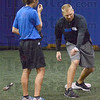 Interaction: Indiana State University head softball coach Shane Bouman works with Megan Stone during Friday's practice at their indoor facility.