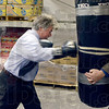 Tribune-Star/Joseph C. Garza<br /> Take that, hunger!: Indiana Attorney General Greg Zoeller throws a right into a punching bag to symbolically knock out hunger after a press conference at Catholic Charities Tuesday. Holding the bag is Catholic Charities Director John Etling.