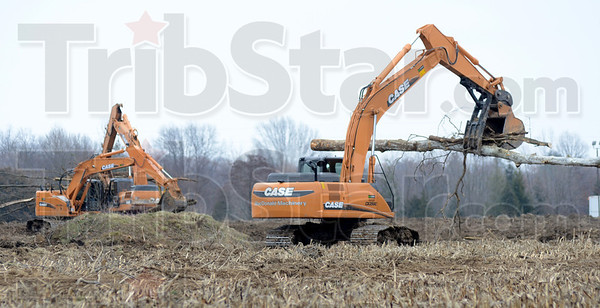 Tribune-Star/Jim Avelis<br /> Clearing a path: Excavators move downed trees to a brush pile along the path of the 641 bypass near Riley Road and Indiana 46 Tuesday afternoon.