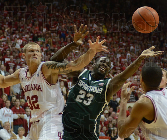 Indiana's Derek Elston and Michigan State's Draymond Green reach for a loose ball during the Hoosiers' game against the Spartans Tuesday in Bloomington.