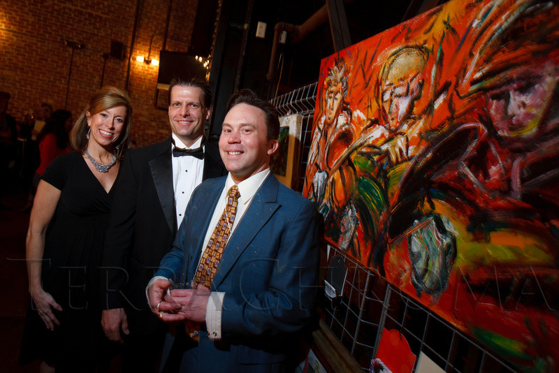 """Jean and Matt Bushong targeted the acrylic painting by Eric Matelski (right).  """"ArtReach Dine & D'art,"""" benefiting ArtReach Denver, at Mile High Station in Denver, Colorado, on Saturday, Feb. 4, 2012.<br /> Photo Steve Peterson"""
