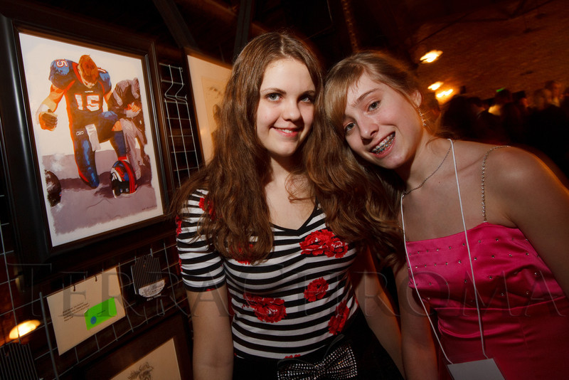 """Volunteer Sophia Johnson-Grimes with Clare Caraghar, picked her favorite painting of Tim Tebow.  """"ArtReach Dine & D'art,"""" benefiting ArtReach Denver, at Mile High Station in Denver, Colorado, on Saturday, Feb. 4, 2012.<br /> Photo Steve Peterson"""