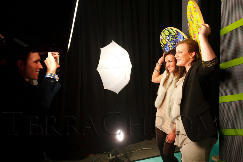 "xxx uses a smartphone to take photos of Tarrin Miller and Lauren Lipman getting creative with a few props on a small set.  Design After Dark 2012, themed ""bespoke,"" benefiting the Denver Art Museum, at 445 Broadway in Denver, Colorado, on Friday, Feb. 10, 2012.<br /> Photo Steve Peterson"