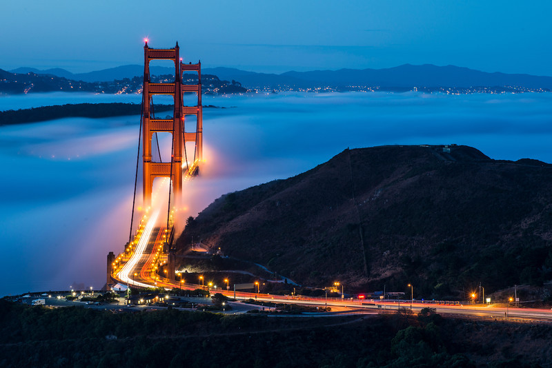 "Fog on this particular morning was quite the surprise. Alan, Willie and I met up in San Francisco with the original idea of shooting a cloudy sunrise somewhere in San Francisco. By the time we arrived in the city the clouds had moved northeast and we decided to cross the Golden Gate Bridge to find a westerly spot to photograph. As we crossed the bridge into Marin we started to get excited -- there was a small layer of fog forming and we hoped it would keep coming in. We stopped at Battery Spencer but decided to keep driving. <br /> <br /> For the last 6 months Alan had an idea of trying to shoot a low fog photograph with the 2 towers aligned. The only problem is that you have to hike for quite a while to make it to the location and most people don't wake up early enough. Fortunately for us we had arrived much earlier than anticipated and if we booked it we would make it before sunrise. By the time we arrived at Alan's spot a much denser fog had rolled in and started covering most of the bridge. <br /> <br /> We were all pretty excited as we began shooting. Looking at the photos in our cameras showed a beautiful glow in the fog, some nice purple and blue tones, and the wonderful bridge. We shot the bridge with the 2 towers aligned first and then later moved back and to the right to shoot the bridge with a slight angle. Blue hour only lasted about 10 minutes and we ran around like crazy men trying to shoot different compositions. Ultimately I liked the slightly non-aligned photo the best, showing more of the bridge and giving insight into how the fog covered and exposed the beautiful Golden Gate Bridge. I titled this ""Dancing Gateway"" because I like the way that the fog seems to dance in and out of the bridge.<br /> <br /> Our morning concluded with a beautiful sunrise as the clouds lit up in beautiful oranges and reds. 16 photos stitched into a 230 megapixel image were required to fit the entire scene in. One day when I have time to stitch the photo together properly I might even show you what it looked like!<br /> <br /> Nikon D800 w/Nikkor 70-300mm f/4.5-5.6G ED-IF AF-S VR<br /> 220mm, f/11, 30 sec, ISO 160"