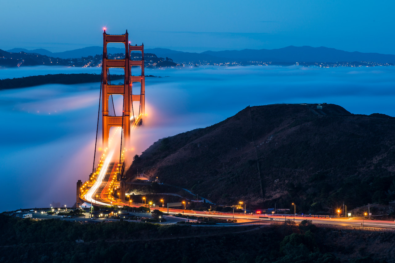 """Fog on this particular morning was quite the surprise. Alan, Willie and I met up in San Francisco with the original idea of shooting a cloudy sunrise somewhere in San Francisco. By the time we arrived in the city the clouds had moved northeast and we decided to cross the Golden Gate Bridge to find a westerly spot to photograph. As we crossed the bridge into Marin we started to get excited -- there was a small layer of fog forming and we hoped it would keep coming in. We stopped at Battery Spencer but decided to keep driving.   For the last 6 months Alan had an idea of trying to shoot a low fog photograph with the 2 towers aligned. The only problem is that you have to hike for quite a while to make it to the location and most people don't wake up early enough. Fortunately for us we had arrived much earlier than anticipated and if we booked it we would make it before sunrise. By the time we arrived at Alan's spot a much denser fog had rolled in and started covering most of the bridge.   We were all pretty excited as we began shooting. Looking at the photos in our cameras showed a beautiful glow in the fog, some nice purple and blue tones, and the wonderful bridge. We shot the bridge with the 2 towers aligned first and then later moved back and to the right to shoot the bridge with a slight angle. Blue hour only lasted about 10 minutes and we ran around like crazy men trying to shoot different compositions. Ultimately I liked the slightly non-aligned photo the best, showing more of the bridge and giving insight into how the fog covered and exposed the beautiful Golden Gate Bridge. I titled this """"Dancing Gateway"""" because I like the way that the fog seems to dance in and out of the bridge.  Our morning concluded with a beautiful sunrise as the clouds lit up in beautiful oranges and reds. 16 photos stitched into a 230 megapixel image were required to fit the entire scene in. One day when I have time to stitch the photo together properly I might even show you what it looke"""