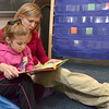 Tribune-Star/Joseph C. Garza<br /> Getting cozy with a good book: Lost Creek Elementary School special education teacher Carol Crawn reads a book to Abby Goodall during class Thursday at the eastside school. Crawn is pursuing her master's degree online through WGU.