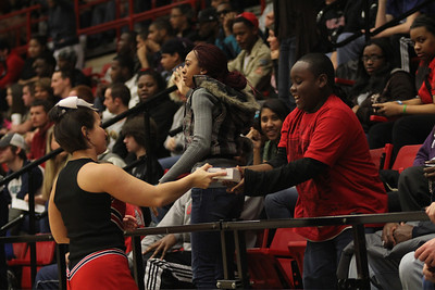 A child receives a free pizza from a cheerleader.