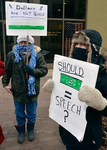 Tribune-Star/Joseph C. Garza<br /> Corner occupation: Occupy Terre Haute participant Heather Hindle, right, displays a sign near the corner of Sixth Street and Wabash Avenue Friday with other participants.