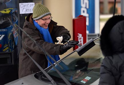 Tribune-Star/Joseph C. Garza<br /> Not even a brisk wind could stop him: Steve Witt cleans the windshield of a customer's car at the Baesler's Market gas pumps Friday as part of the United Day for the United Way.